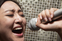 Close-up of young woman singing into a microphone at karaoke Royalty Free Stock Image