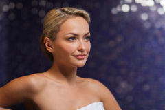 Close up of young woman sitting in bath towel. People, beauty, spa, healthy lifestyle and relaxation concept - close up of beautiful young woman sitting in bath Stock Image