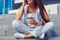 Close-up of young woman sitting with crossed legs and talking o Stock Images