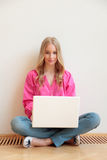 Close-up of young woman sitting on floor and using laptop Stock Images