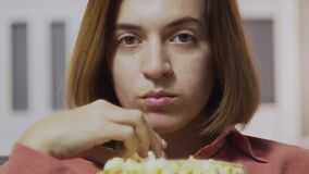 Close up of young woman sitting on the sofa, eating popcorn and watching TV