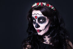 Close up of young woman with skull make up and flowers in hair Stock Photo