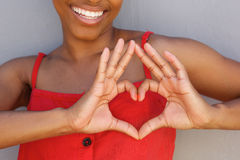 Close up young woman smiling with heart shape hand sign Royalty Free Stock Photography