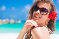 Close up of young woman in sunglasses putting sun cream on shoulder Royalty Free Stock Photo