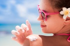 Close up of young woman in sunglasses putting sun Royalty Free Stock Images