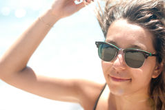 Close-up of a young woman with sunglasses sunlight. On the beach Royalty Free Stock Images