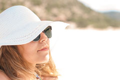 Close-up of a young woman with sunglasses sunlight. On the beach Stock Photography
