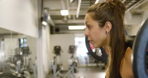 Close-up of a sporty woman training squat with heavy weights in fitness gym. Close-up of a young woman training squat strength with heavy weights on her stock video footage