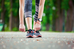 Close up of young woman tying her laces before a run. Stock Photos