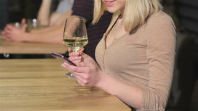 Close up of a young woman uses smartphone at the bar. Close up of female using smartphone at the bar. Blonde woman holding white smartphone in her hand at the stock video footage