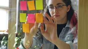 Close-up of young attractive woman wearing glasses sticking colored memos on glass board in modern office. She is. Close-up of young woman wearing glasses stock video