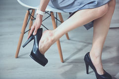 Close up of young woman wearing hills. Unsuitable shoes. Young slim woman sitting on the chair and taking off hills Stock Images