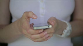 Close up of young woman white dress fingers typing on her smartphone. Slow motion stock footage