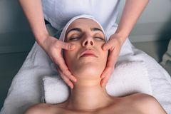 Woman receiving facial treatment on clinical center. Close up of young women with closed eyes receiving facial massage on a clinical center. Medicine, healthcare royalty free stock image