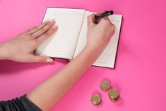 Woman hand holds a pen in hand and wrote next to the coin on pink background stock photography