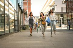 Close up of young woman jumping on street with shopping bag. royalty free stock photos