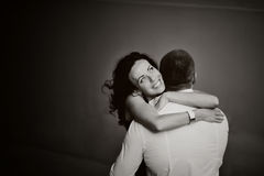 Young woman tenderly embracing her boyfriend. Close-up of a young women tenderly embracing her boyfriend, black and white Stock Image