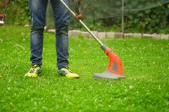 Close up of young worker with a string lawn trimmer mower cutting grass in a blurred nature background.  Stock Images