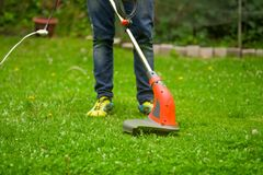Close up of young worker with a string lawn trimmer mower cutting grass in a blurred nature background.  Stock Photography