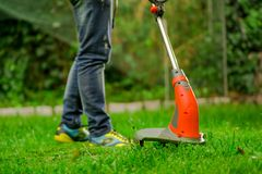 Close up of young worker wearing jeans and using a lawn trimmer mower cutting grass in a blurred nature background.  Royalty Free Stock Photos