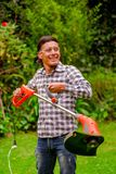 Close up of young worker wearing transparent glasses protection and holding a lawn trimmer mower cutting grass in a. Blurred nature background Stock Photo
