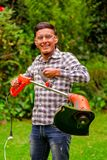 Close up of young worker wearing transparent glasses protection and holding a lawn trimmer mower cutting grass in a. Blurred nature background Royalty Free Stock Images