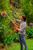 Close up of young worker wearing transparent glasses protection and holding a lawn trimmer mower cutting some bushes, in. A blurred nature background Royalty Free Stock Images