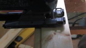 Close-up zagende figuurzaag in de raad, het proces om de raad te snijden stock videobeelden