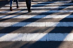 Close up zebra crossing foreground pedestrians long shadows junction street feet. Close up of zebra crossing on foreground with pedestrians making long shadows Stock Image