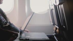 Close-up zijaanzicht die van vliegtuigpassagier het letten op video's op het mobiele apparaat van de tablet videospeler, het leid stock videobeelden