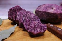Close-up zijaanzicht van blauwe aardappels, die in golvende cirkels worden gesneden Verse groenten voor uitstekende immuniteit stock afbeeldingen
