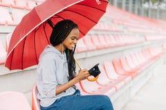 Close-up zijportret van het blije Afro-Amerikaanse meisje die via de mobiele telefoon texting terwijl het zitten onder paraplu op royalty-vrije stock afbeelding