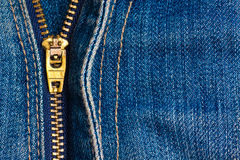Close up of a zipper over blue denim Royalty Free Stock Image