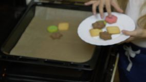 Close up zoom in handheld. Young caucasian girl put cookies from oven to white plate. Home made cookies. Indoors kitchen stock video