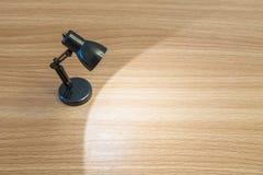 Close-up zwarte kleine lamp met licht in de donkere ruimte op houten bureau geweven achtergrond met exemplaarruimte Stock Afbeeldingen