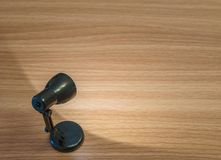 Close-up zwarte kleine lamp met licht in de donkere ruimte op houten bureau geweven achtergrond met exemplaarruimte Royalty-vrije Stock Fotografie