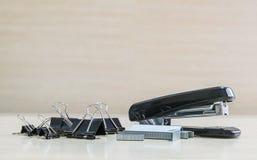 Close-up zwarte nietmachine en zwarte zegelpaperclip, kantoorbenodigdheden op vaag houten bureau en muur in geweven backgrou van  Royalty-vrije Stock Foto