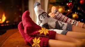 Close-upbeeld die van familie in warme gebreide sokken naast open haard en Kerstboom liggen stock afbeeldingen