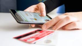 Close-upbeeld die van jonge vrouw online orde op smartphone maken en met creditcard betalen stock foto