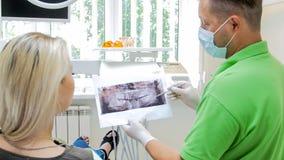 Close-upbeeld die van tandarts x-ray beeld van tanden verklaren aan zijn patiënt royalty-vrije stock foto's