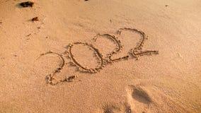 Close-upbeeld van 2022 die Nieuwjarenaantallen op nat zand op het strand worden geschreven stock foto