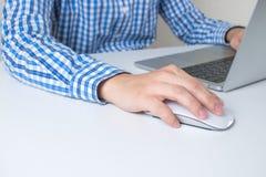 Close-upbeeld van een mens die een blauw plaidoverhemd dragen die een hand gebruiken die de muis in het bureau houden royalty-vrije stock foto