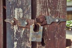 Close-upbeeld van een uitstekend geroest slot op een oude versleten houten omheining royalty-vrije stock foto's