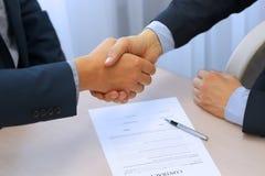 Close-upbeeld van een vaste handdruk tussen twee collega's na het ondertekenen van een contract Royalty-vrije Stock Afbeelding