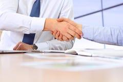 Close-upbeeld van een vaste handdruk tussen twee collega's na het ondertekenen van een contract Stock Afbeelding