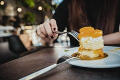 Close-upbeeld van een vrouw die een oranje cake met vork op witte plaat op houten lijst snijden royalty-vrije stock afbeelding