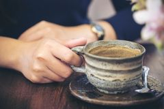 Close-upbeeld van een vrouwen` s hand die een kop van koffie op houten lijst houden Royalty-vrije Stock Afbeeldingen