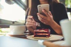 Close-upbeeld van een vrouwenholding, gebruikend en bekijkend slimme telefoon terwijl het eten van een cake met witte koffiekoppe stock fotografie
