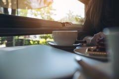 Close-upbeeld van een vrouwenzitting in koffie terwijl het eten van een cake met witte koffiekoppen en laptop Royalty-vrije Stock Foto