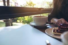 Close-upbeeld van een vrouwenzitting in koffie terwijl het eten van een cake met witte koffiekoppen en laptop Stock Fotografie
